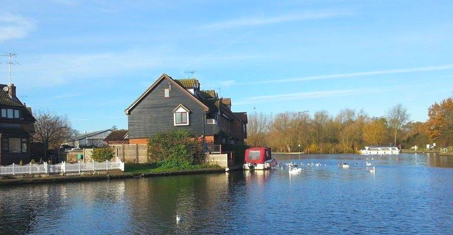 Looking upstream along the River Bure in Wroxham with cottages in foreground